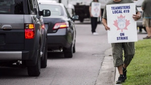 Striking workers are seen picketing at Pearson International Airport in Toronto on Friday July 29, 2017. (Christopher Katsarov / THE CANADIAN PRESS)