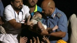Rescuers pull out 7-month-old boy Pasquale from the rubble of a collapsed building in Casamicciola, on the island of Ischia, near Naples, Italy, a day after a 4.0-magnitude quake hit the Italian resort island, Tuesday, Aug. 22, 2017. (ANSA via AP)