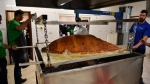 Muslim Aid staff and volunteers work as they attempt to construct and cook the world's largest samosa at the East London Mosque in London on August 22, 2017. (© BEN STANSALL / AFP)