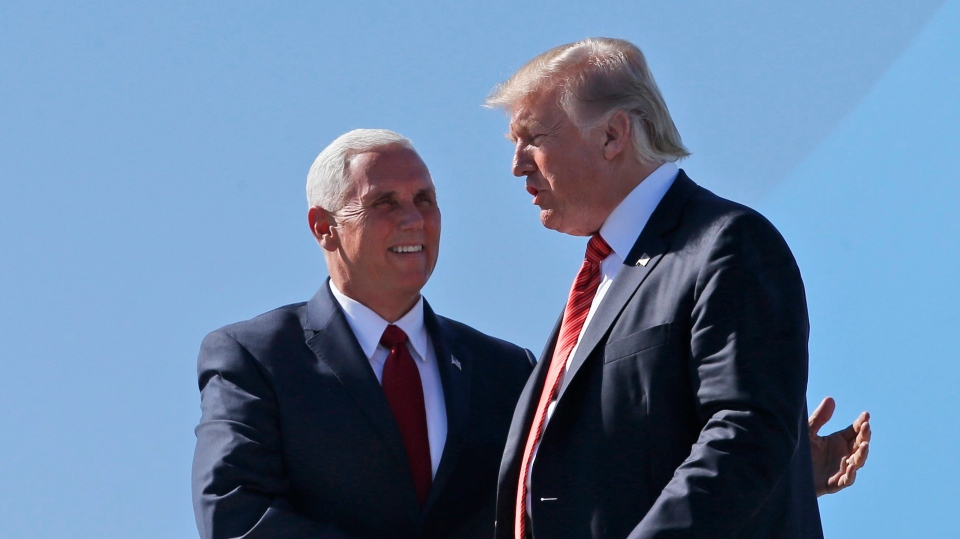 U.S. Vice President Mike Pence, left, greets President Donald Trump as he steps off Air Force One as he arrives Tuesday, Aug. 22, 2017, in Phoenix. (AP / Alex Brandon)