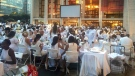 Guests clad in white sit down to a pop-up dinner at New York's Lincoln Center on Tuesday, Aug. 22, 2017. (AP / Julie Walker)