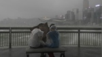 People play with strong wind caused by Typhoon Hato on the waterfront of Victoria Harbour in Hong Kong on Wednesday, Aug. 23, 2017. (AP / Vincent Yu)