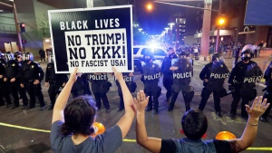 Protesters raise their hands after Phoenix police used tear gas outside the Phoenix Convention Center, in Phoenix, Tuesday, Aug. 22, 2017. Protests were held against President Donald Trump as he hosted a rally inside the convention center. (AP Photo/Matt York)