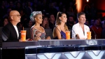 In this Tuesday, Aug. 22, 2017 photo provided by NBC, judges Howie Mandel, Mel B, Heidi Klum and Simon Cowell participate in a live broadcast of 'America's Got Talent' in Los Angeles. Mel B threw a cup of water on Cowell and walked off the stage after Cowell made a joke about her wedding night during the show. (Trae Patton/NBC via AP)