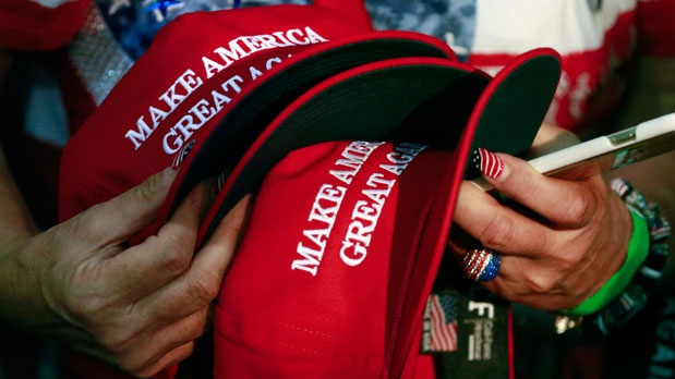 In this June 2, 2016, file photo, a woman holds hats to get them autographed by Republican presidential candidate Donald Trump during a rally in San Jose, Calif. (AP Photo/Jae C. Hong, File)