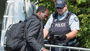 An asylum seeker, claiming to be from Eritrea, shows his passport to an RCMP officer as crosses the border into Canada from the United States Monday, August 21, 2017 near Champlain, N.Y. (Paul Chiasson / THE CANADIAN PRESS)
