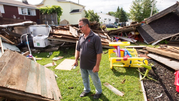 Michel Laurin surveys the damage to his backyard from a category one tornado in Lachute, Que., northwest of Montreal, Wednesday, Aug. 23, 2017. (Ryan Remiorz / THE CANADIAN PRESS)