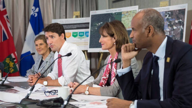 Prime Minister Justin Trudeau is joined by Laura Albanese (left), Ontario Minister of Citizenship, Kathleen Weil, Quebec Minister of Immigration, Diversity and Inclusiveness, and Ahmed Hussen, right, Federal Minister of Immigration, Refugees and Citizenship, in a meeting of the Intergovernmental Task Force on Irregular Migration, Wednesday, August 23, 2017 in Montreal. (THE CANADIAN PRESS/Paul Chiasson)
