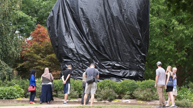 Residents and visitors look over the covered Ce statue of Confederate General Robert E. Lee in Emancipation park in Charlottesville, Va., Wednesday, Aug. 23, 2017. The move to cover the statues is intended to symbolize the city's mourning for Heather Heyer, killed while protesting a white nationalist rally earlier this month. (AP Photo / Steve Helber)