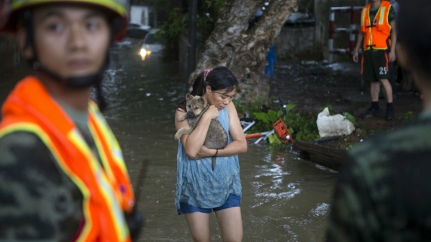 A woman holds on to her pet as they evacuate from flood waters caused by Typhoon Hato and the tide in Guangzhou in southern China's Guangdong province on Wednesday Aug. 23, 2017. (Chinatopix)