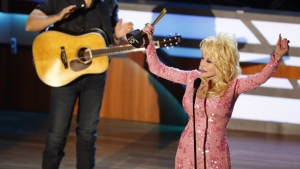 Dolly Parton reacts after receiving the Gary Haber Lifting Lives awards Brad Paisley looks on during the 11th annual ACM Honors at the Ryman Auditorium on in Nashville, Tenn. on Wednesday, Aug. 23, 2017. (Wade Payne / Invision)