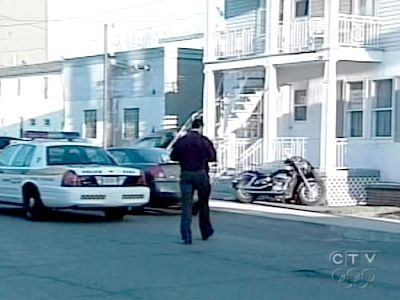 A Quebec Provincial Police officer walks towards a home in Sorel, Que., that was involved in a crackdown on the Hell's Angers on Wednesday, April 15, 2009.