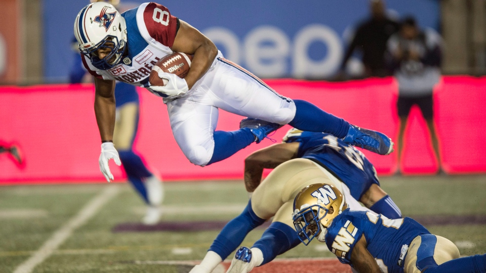 Montreal Alouettes slotback Nik Lewis, left, leaps over Winnipeg Blue Bombers defensive back Taylor Loffler (16) during first half CFL football action, in Montreal, on Thursday, August 24, 2017. (THE CANADIAN PRESS/Paul Chiasson)