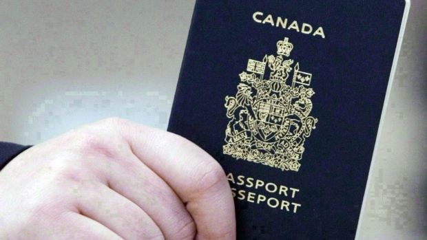 A passenger holds a Canadian passport before boarding a flight in Ottawa on Jan 23, 2007. THE CANADIAN PRESS/Tom Hanson