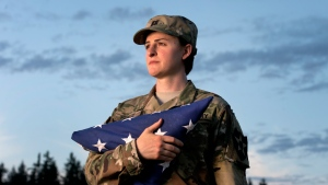 In this Aug. 28, 2015 file photo, Capt. Jennifer Peace holds a flag as she stands for a photo near her home in Spanaway, Wash. P (Drew Perine/The News Tribune via AP, File )