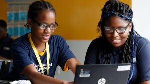 Jahiem Johnson, 13, left, helps classmate Kamya Saunders, 13, as they work on an English passage during class at the Washington Leadership Academy in Washington, Wednesday, Aug. 23, 2017. (AP Photo/Jacquelyn Martin)