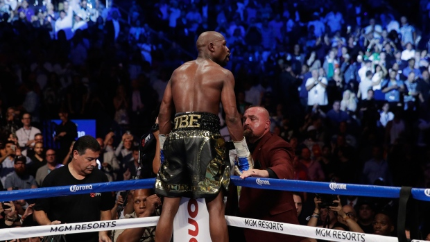 Floyd Mayweather Jr. poses for photographers after defeating Conor McGregor in a super welterweight boxing match Saturday, Aug. 26, 2017, in Las Vegas. (AP Photo / Isaac Brekken)