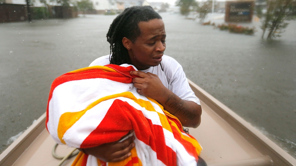 Demetres Fair holds a towel over his daughter Damouri Fair, 2, as they are rescued by boat by members of the Louisiana Department of Wildlife and Fisheries and the Houston Fire Department during flooding from Tropical Storm Harvey, which hit Texas last week as a Category 4 hurricane, in Houston, Monday, Aug. 28, 2017. (AP Photo/Gerald Herbert)