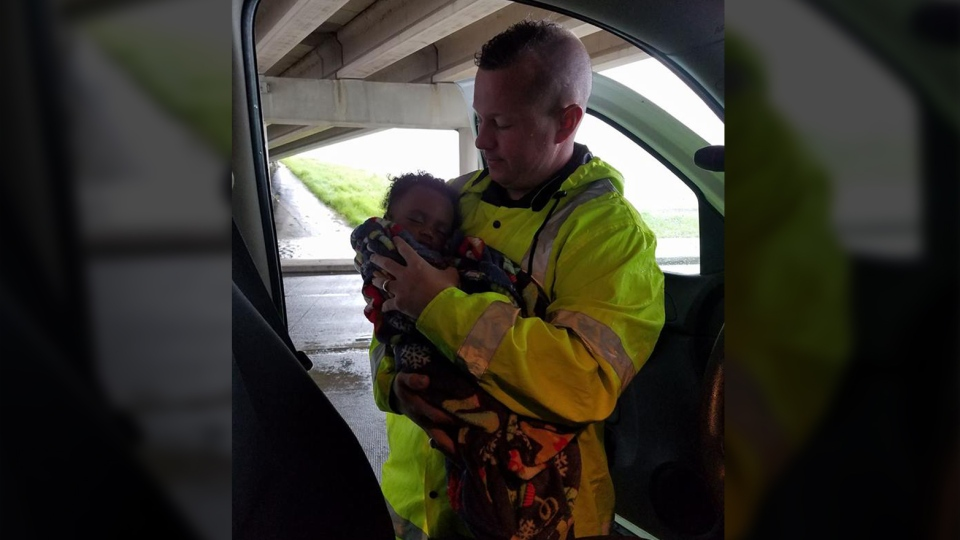 A photo of Cpl. Reed Clark cradling the baby went viral on Facebook. (Constable Christopher E. Diaz/Facebook)
