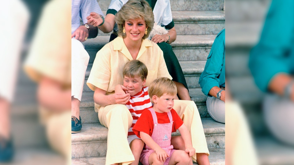 In this Aug. 9, 1987 file photo, Britain's Princess Diana of Wales smiles as she sits with her sons, Princes Harry, front, and William, on the steps of the Royal Palace on the island of Mallorca, Spain, where the British Royal family is on holiday with the Spanish King Juan Carlos and his family.  (AP Photo/John Redman, File)
