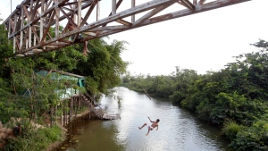 In this Sept. 22, 2011 file photo, a youth jumps from an overpass into a river in Paragominas, northern state of Para, Brazil. (AP Photo/Andre Penner, File)