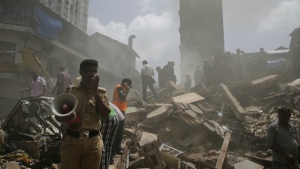 A policeman makes an announcement on a loudspeaker at the site of building collapse in Mumbai, India on Thursday, Aug. 31, 2017. (AP / Rafiq Maqbool)