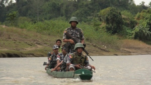 In this Friday, July 14, 2017, photo, Myanmar Border Guard Police (BGP) officers travel in a wooden boat operated by Rohingya Muslim men at Tin May village in which Myanmar government and military claim the existence of alleged Muslim terrorists in Buthidaung, Rakhine State, Myanmar. (AP Photo/ Esther Htusan)