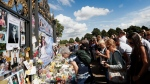 People crowd around the gates of Kensington Palace in London to pay tribute to the late Diana, Princess of Wales, Thursday, Aug. 31, 2017. (AP / Kirsty Wigglesworth)
