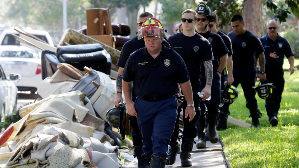 Firefighters walk around debris removed from homes during a door-to-door survey of a neighborhood that was hit by floodwaters from Tropical Storm Harvey in Houston, Thursday, Aug. 31, 2017. The first responders are checking homes for any emergency needs of residents. (AP Photo / LM Otero)