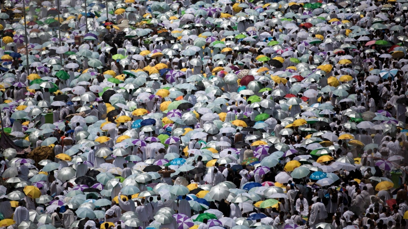 Muslim pilgrims hold umbrellas as they attend noon prayers outside the Namirah mosque on Arafat Mountain, during the annual hajj pilgrimage, outside the holy city of Mecca, Saudi Arabia, Thursday, Aug. 31, 2017. (AP Photo/Khalil Hamra)