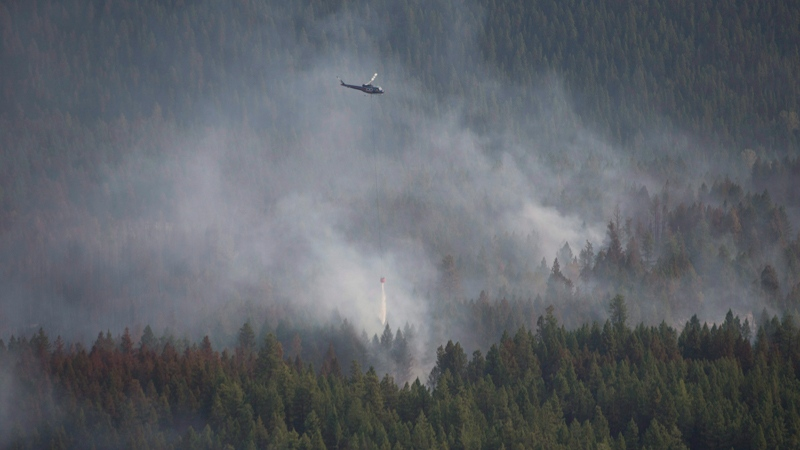 A helicopter dumps a load of water on the Philpot Road fire outside of Kelowna, B.C., Monday, August 28, 2017. THE CANADIAN PRESS/Jonathan Hayward