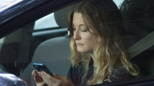 FILE - In this Wednesday, June 22, 2016, file photo, a driver uses her mobile phone while sitting in traffic in Sacramento, Calif. (AP Photo/Rich Pedroncelli)