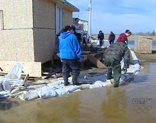 Volunteers fortify a sandbag dike while wading through flood waters at Manitoba's Peguis First Nation on Thursday, April 16, 2009.