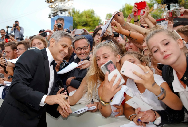 "Actor George Clooney poses for a selfie photo while he signs autographs on the red carpet of the film ""Suburbicon"" at the 74th Venice FilmFestival in Venice, Italy, Saturday, Sept. 2, 2017. (AP Photo / Domenico Stinellis)"