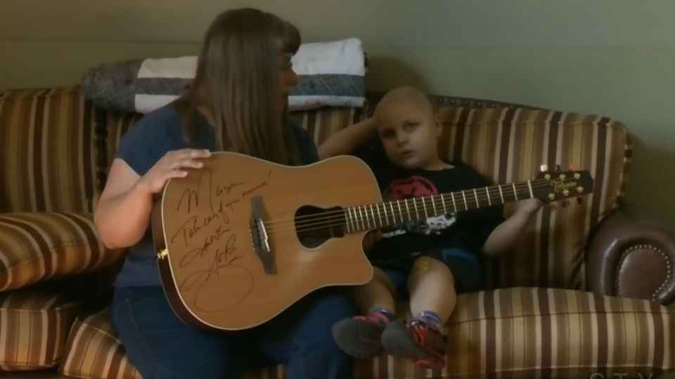Garth Brooks Stops Calgary Show To Gift Guitar To Mother Of Young