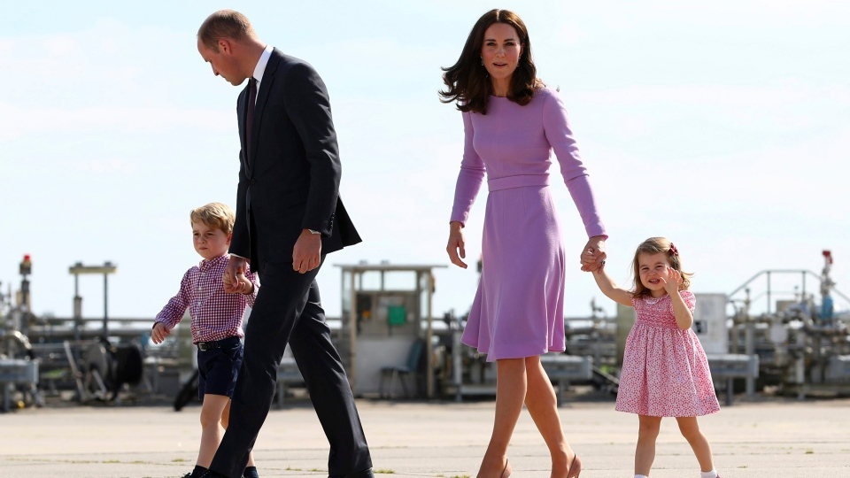In this Friday, July 21, 2017 file photo Prince William, second left, and his wife Kate, the Duchess of Cambridge, second right, and their children, Prince George, left, and Princess Charlotte, right are on their way to board a plane in Hamburg, Germany. (Christian Charisius/Pool Photo via AP)