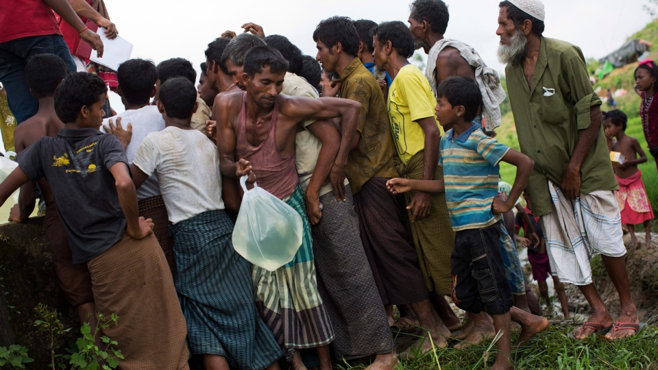 Rohingyas living in no man's land collect water donated by Bangladesh Red Crescent members, near Cox's Bazar's Tumbru area, Sept. 4, 2017. (Bernat Armangue/AP)