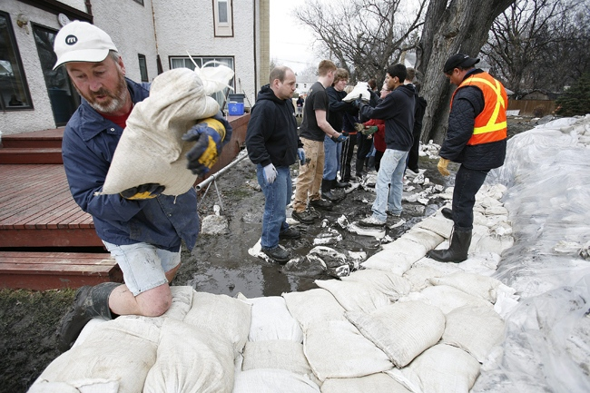 Greg Locke and other volunteers help build dikes on on Scotia Street in Winnipeg's north end Thursday, April 16, 2009. (John Woods / THE CANADIAN PRESS)