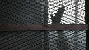 A Muslim Brotherhood member gestures from a defendant's cage in a courtroom in Torah prison, southern Cairo, Egypt on Aug. 22, 2015. (AP / Amr Nabil)