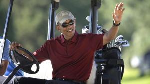 Barack Obama waves from a golf cart at Farm Neck Golf Club, in Oak Bluffs, Mass., on Aug. 14, 2015. (Steven Senne / AP)