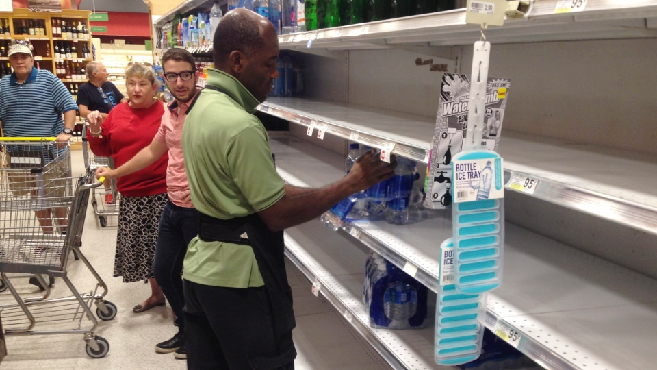 An employee restocks bottled water on bare shelves as customers look on at a Publix grocery store, Tuesday, Sept. 5, 2017, in Surfside, Fla. (AP Photo/Wilfredo Lee)