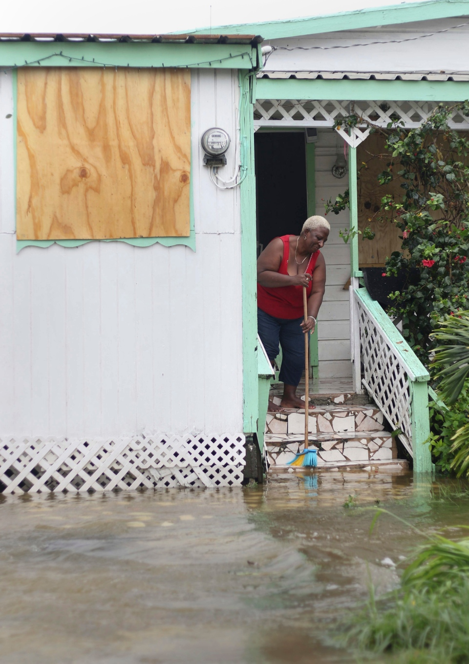 A woman pushes out floodwaters on her property after the passing of Hurricane Irma, in St. John's, Antigua and Barbuda, Wednesday, Sept. 6, 2017. (AP Photo/Johnny Jno-Baptiste)