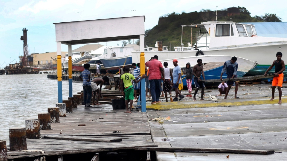 People recover broken parts of the dock after the passing of Hurricane Irma, in St. John's, Antigua and Barbuda, Wednesday, Sept. 6, 2017.  (AP Photo/Johnny Jno-Baptiste)