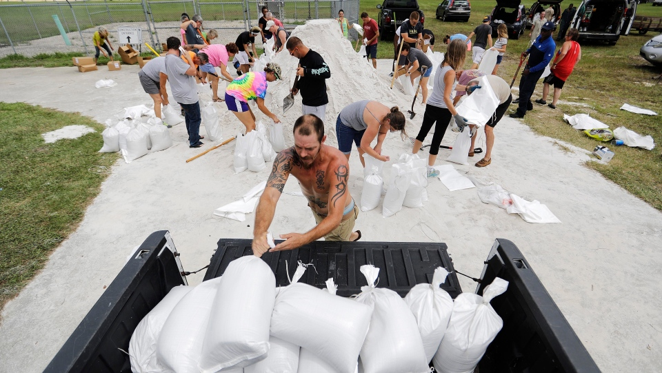 Ryan Kaye loads sandbags into his truck at a makeshift filling station provided by the county as protection ahead of Hurricane Irma, Friday, Sept. 8, 2017, in Palm Coast, Fla. (AP Photo/David Goldman)