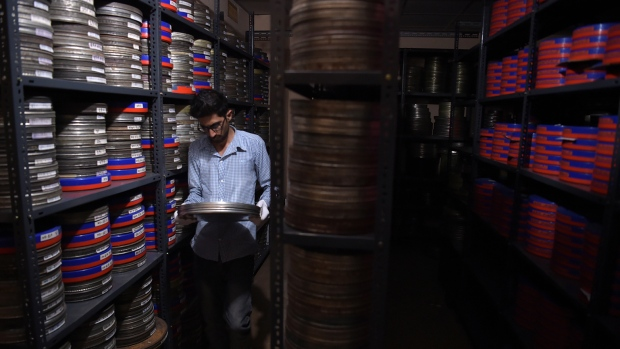 An employee taking a film reel to be digitised at the state-run Afghan Film department in Kabul. (Shah Marai/AFP)