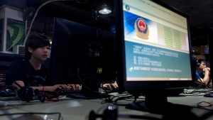 In this Aug. 19, 2013 file photo, computer users sit near a monitor display with a message from the Chinese police on the proper use of the Internet at an Internet cafe in Beijing, China. (AP Photo/Ng Han Guan, File)