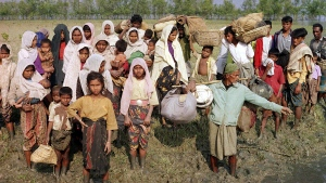 In this Feb. 2, 1992, file photo, Burmese Muslims fleeing the military government arrive in Bangladesh by boat across Naff River. (AP Photo/Kamrul Huda, File)