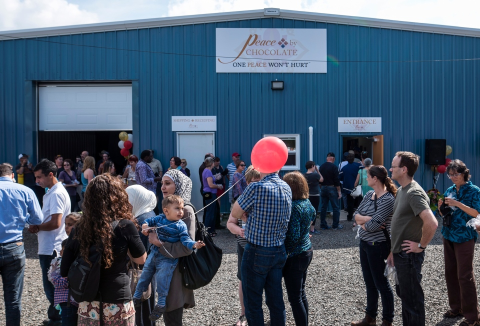 Members of the community line up outside of Peace By Chocolate's factory while waiting to tour the newly-opened facility in Antigonish, N.S. on Saturday, September 9, 2017. THE CANADIAN PRESS/Darren Calabrese