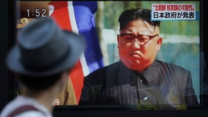 A man watches a TV news program on a public screen showing an image of North Korean leader Kim Jong Un while reporting North Korea's possible nuclear test in Tokyo Sunday, Sept. 3, 2017. (AP / Eugene Hoshiko)
