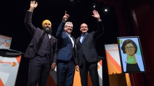 Jagmeet Singh, from left to right, Charlie Angus and Guy Caron pose for a photograph as Niki Ashton, is seen on a television screen via satellite from Ottawa, before the final federal NDP leadership debate in Vancouver, B.C., on Sunday, September 10, 2017. THE CANADIAN PRESS/Darryl Dyck